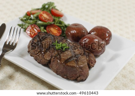 cooked filet mignon steak in a white plate with salad and little potatoes. Shallow depth of field. - stock photo