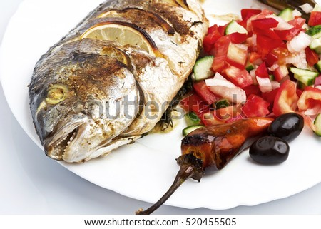 Cooked fish sea bream fish with lemon, parsley,garlic.