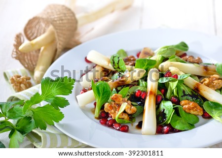 Cooked fresh white asparagus on lamb's lettuce with candied walnuts, pomegranate seeds and balsamic vinegar - stock photo