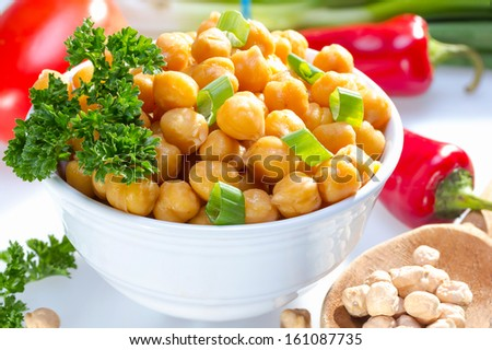 Cooked garbanzo beans (chick peas) in a bowl served with raw vegetables. - stock photo