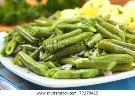 Cooked green beans with onion and parsley with cooked potato in the back (Selective Focus, Focus one third into the beans) - stock photo