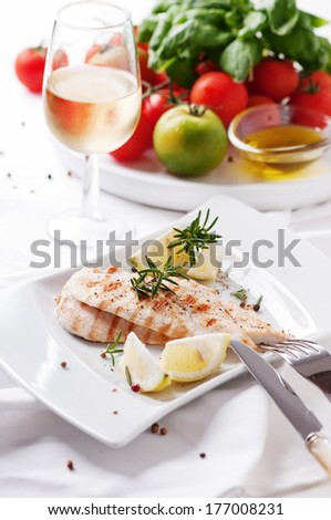 Cooked healthy chicken fillet with lemon and rosemary, selective focus