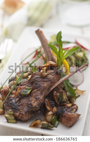 Cooked lamb chops garnished with fresh herbs - stock photo