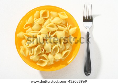 Cooked macaroni shells, served without sauce an orange plate on white background. Close up, top view, high resolution product. - stock photo