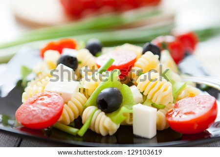 cooked macaroni with vegetables and feta, closeup