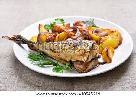 Cooked mackerel fish with potato wedges on white plate - stock photo