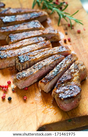 Cooked Medium Grass Fed Beef Steak Sliced in Long Pieces - stock photo