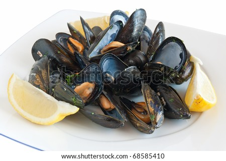 cooked mussels on a plate with lemon isolated on white with clipping path - stock photo