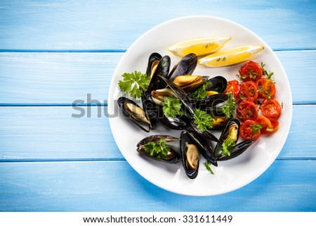 Cooked mussels with lemon and cherry tomatoes  - stock photo
