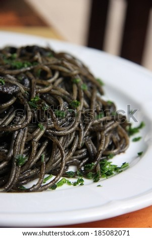 Cooked noodles in black sauce served on a plate. - stock photo