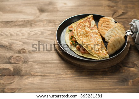 Cooked omelette in a frying pan with the sliced bread for breakfast on wooden table - stock photo