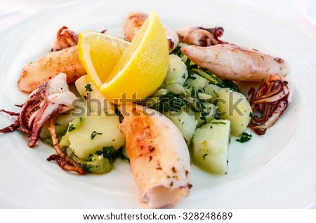 Cooked on the grill calamari with potatoes and lemon