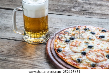 Cooked pizza with a glass of beer - stock photo