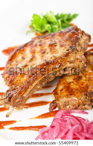Cooked pork chop with kiwi and parsley on a white - stock photo