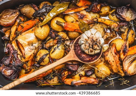 Cooked rabbit stew with  forest mushrooms , roasted vegetables of season and rustic wooden spoon, top view, close up - stock photo