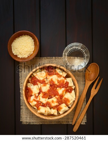 Cooked ravioli with homemade tomato sauce in wooden bowl with grated cheese and glass of water, wooden spoon and fork on the side, photographed overhead on dark wood with natural light - stock photo