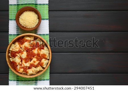 Cooked ravioli with homemade tomato sauce in wooden bowl with grated cheese in small bowl, photographed overhead on dark wood with natural light - stock photo
