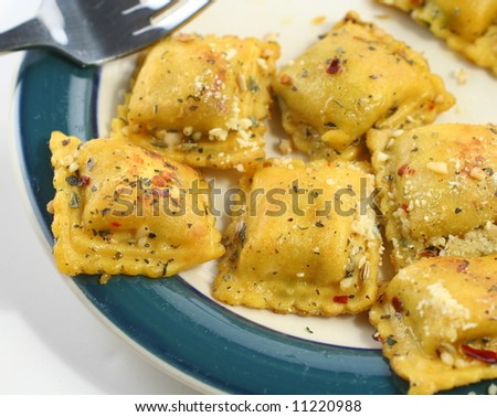 Cooked ravioli with spices on a plate - stock photo