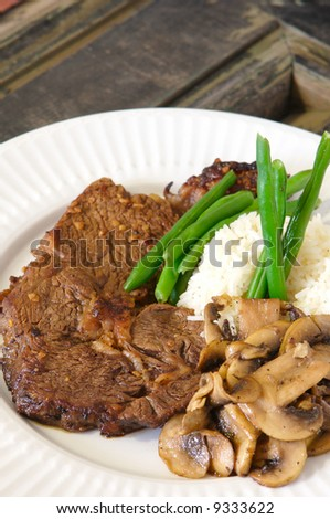 Cooked Rib-eye meal rice green beans and mushrooms - stock photo