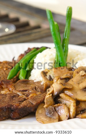 Cooked Rib-eye meal rice green beans and mushrooms close up low level - stock photo