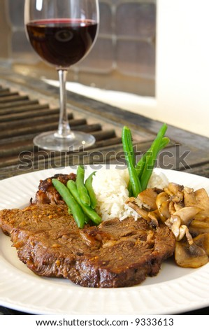 Cooked Rib-eye meal rice green beans and mushrooms close up with red wine out of focus - stock photo