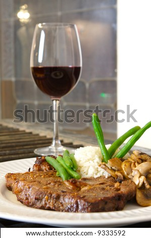Cooked Rib-eye meal rice green beans and mushrooms close up with red wine out of focus shot from a low level room for text