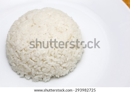 Cooked rice on white dish.