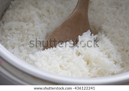 Cooked rice on wooden ladle in electric rice cooker. - stock photo