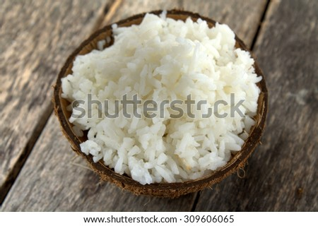 Cooked rice served in coconut shell . Rice is the seed of grass species Oryza sativa. As a cereal grain, most widely consumed staple food of world's human population especially in Asia.