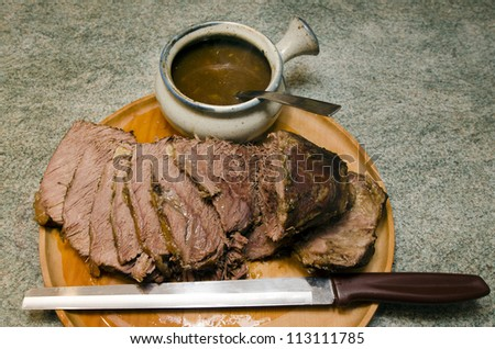 Cooked Roast beef on a cutting meat wooden board with roast beef slicing knife and gravy bowl. - stock photo