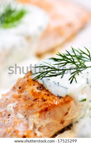 Cooked salmon fillets with dill sauce on white plate - stock photo