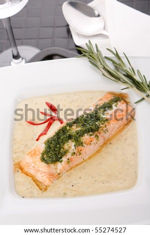 Cooked salmon fillets with  sauce on white plate - stock photo