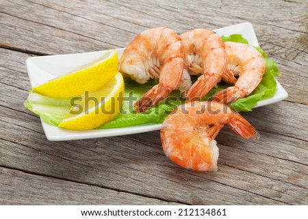 Cooked shrimps with lemon and salad leaves. On wooden table - stock photo