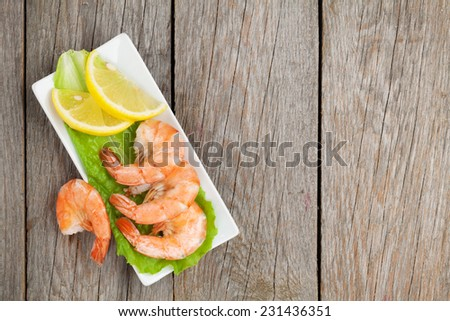 Cooked shrimps with lemon and salad leaves. View from above on wooden table with copy space - stock photo