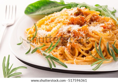 Cooked spaghetti with vegetable sauce, herbs, rosemary and parmesan close-up