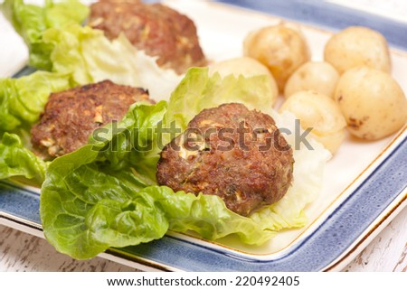 cooked turkey patties with new potatoes and salad - stock photo