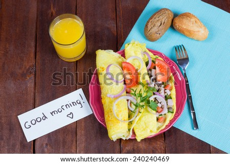 """Cooked with love breakfast for a loved one with a note, """"Good morning."""" Omelet with mushroom and meat filling on a plate. Scrambled eggs, a glass of fresh orange juice, bread and a note. - stock photo"""