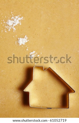 Cookie cutter house on dough with flour clouds - stock photo
