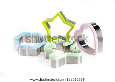 Cookie cutters in various shapes and colours on a white background.