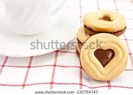 Cookie with chocolate cream and coffee cup - stock photo