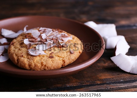 Cookie with coconut chips on plate and rustic wooden table background - stock photo