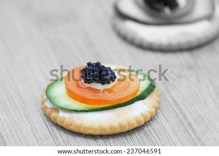 cookie with cream cheese, cucumber, cherry tomato and black vegan caviar, vertical, close-up        - stock photo
