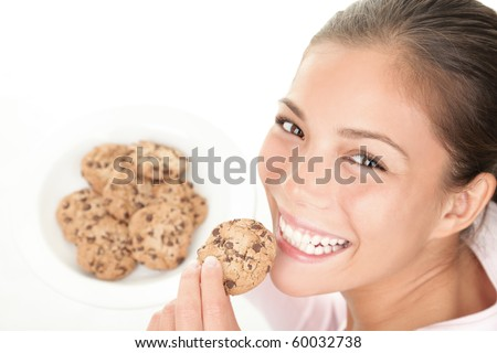 Cookie woman eating chocolate chip cookies. Cute young mixed race chinese / caucasian model on white background. - stock photo