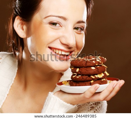 Cookie woman eating chocolate chip cookies on beige  background. - stock photo