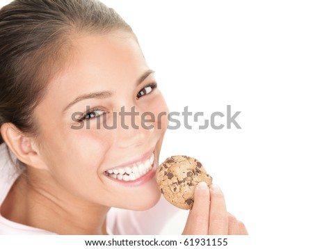 Cookie woman eating chocolate chip cookies on white background. Cute young mixed race chinese / caucasian woman smiling. - stock photo