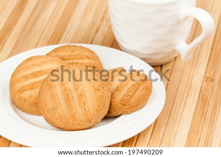 Cookies - A set of fresh, homemade cookies set on a plate with a coffee cup. - stock photo
