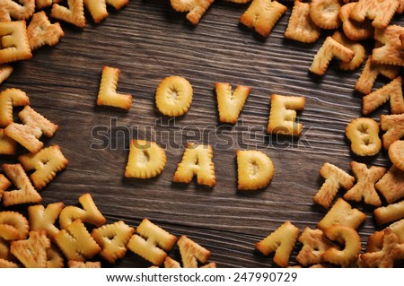 Cookies ABC in the form of word LOVE DAD alphabet on old wood background, Valentines day - stock photo