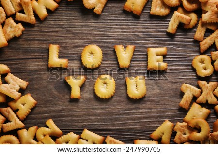 Cookies ABC in the form of word LOVE YOU alphabet on old wood background, Valentines day - stock photo