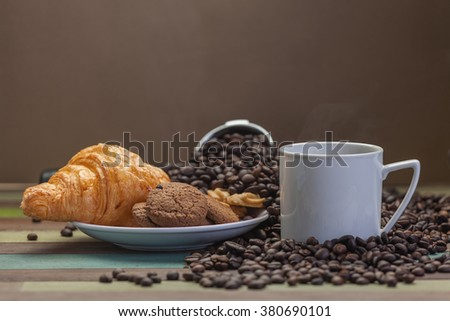 Cookies and coffee cup with beans background - stock photo