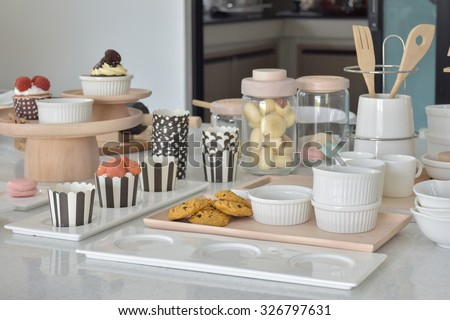 Cookies and cupcakes with cute bake ware setting on white top table